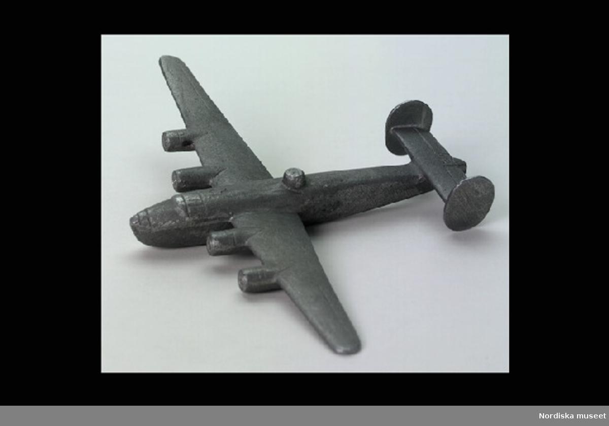 """Inventering Sesam 1996-1999: L 15 cm B 21,5 cm (mellan vingspetsarna) H 2,5 cm Flygplan kallat """"flygande fästning"""". Planet var utformat som ett bombplan från andra världskriget med fyra motorer, kulsprutetorn på kroppens ovansida, två ovala uppåtstående stjärtfenor. Markeringar på flygkroppen för motorfäste, lyktor m.m. Saknar märkning. Ingår i leksakssamling skänkt av fru Ulla Weir. EB 1992"""