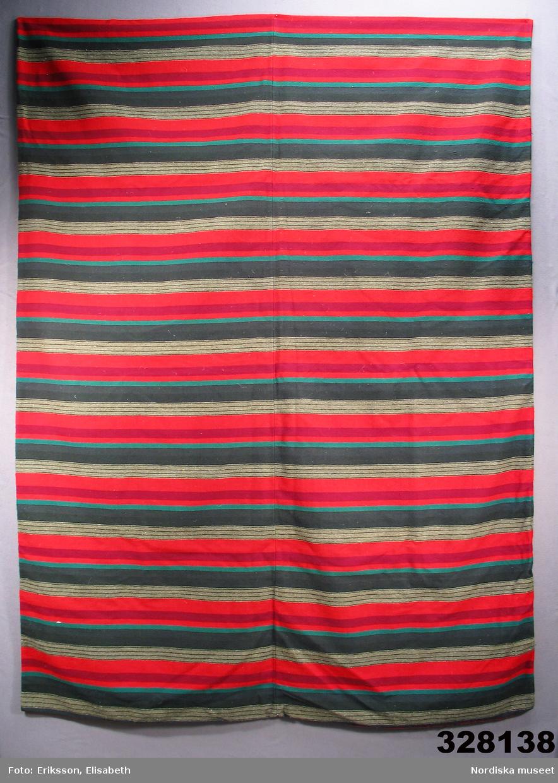 Varp av vitt tvinnat bomullsgarn, inslag i satäng av 1-tr. ullgarn. Randig i kraftiga färger av rött, rödlila, grått och grönt. Vävd i 2 våder och hopsydd i mitten för hand. Har varit fylld med gåsdun. Nyskick, verkar knappt använd. Hör ihop med dynvar inv.nr 328139. Tyget vävt och bolstervaret sytt av Iljena Månsdotter 1849-1929 född i Hagestads sn, Löderup, Ingelstads hd i Skåne, dotter till en välbärgad bonde Måns Olsson. Hon och systern satt under hela tonårstiden och arbetade på sin hemgift med vävning och sömnad. Efter Iljena fanns täcken och dynor i opphämta, dukar med fritt broderi av samma typ som på särken m.m. traditionellt skånskt textilt. Hon gifte sig 1874 med bonden Nils Nilsson och flyttade med välfyllda kistor till gården Stiby 18 i Järrestads hd.  2004-02-18 Berit Eldvik