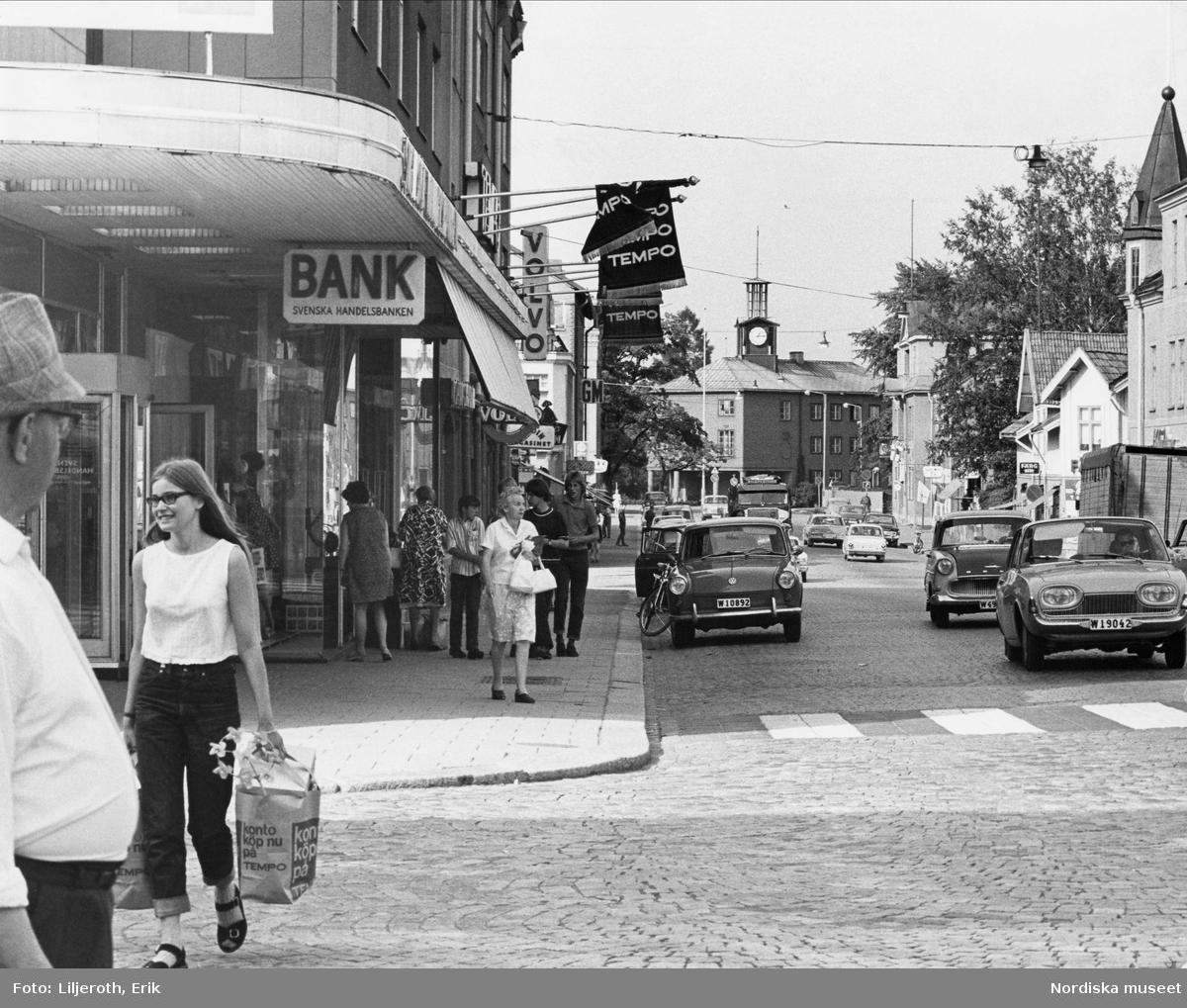 Storgatan i Ludvika centrum, fotgängare och bilar. Handelsbanken, Tempo, Volvo. Längst bort i bild skymtar Ludvika stadshus, som stod färdigt 1937. Huset är ritat av Cyrillus Johansson, stadsarkitekt i Ludvika 1931-1941.