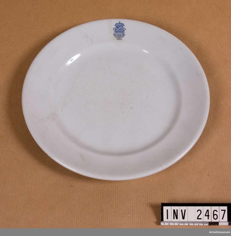 Samhörande nr: 2461-2467. Samhörande nr i gåvan: 2453-97.Tallrik, liten flat, Första livgrenadjärreg. Diam 210 mm. Liten flat tallrik, 1:sta Livgrenadjärregementet,  mässen, I 4.Av gråblå fajans med emblem lilla riksvapnet i blått. I botten  märkt: Gustavsberg .Gåva från stabsavdelningen genom Övljt Lars Märling. Servisen  har tillhört mässen, 1:sta Livgrenadjärregementet.