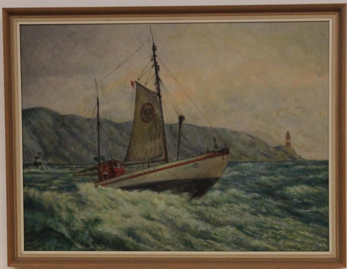 """Redningskøyte 33  """"Larvik"""" går over en bølgetopp. Sjømerke, fyr og landstykke i balgrunnen."""