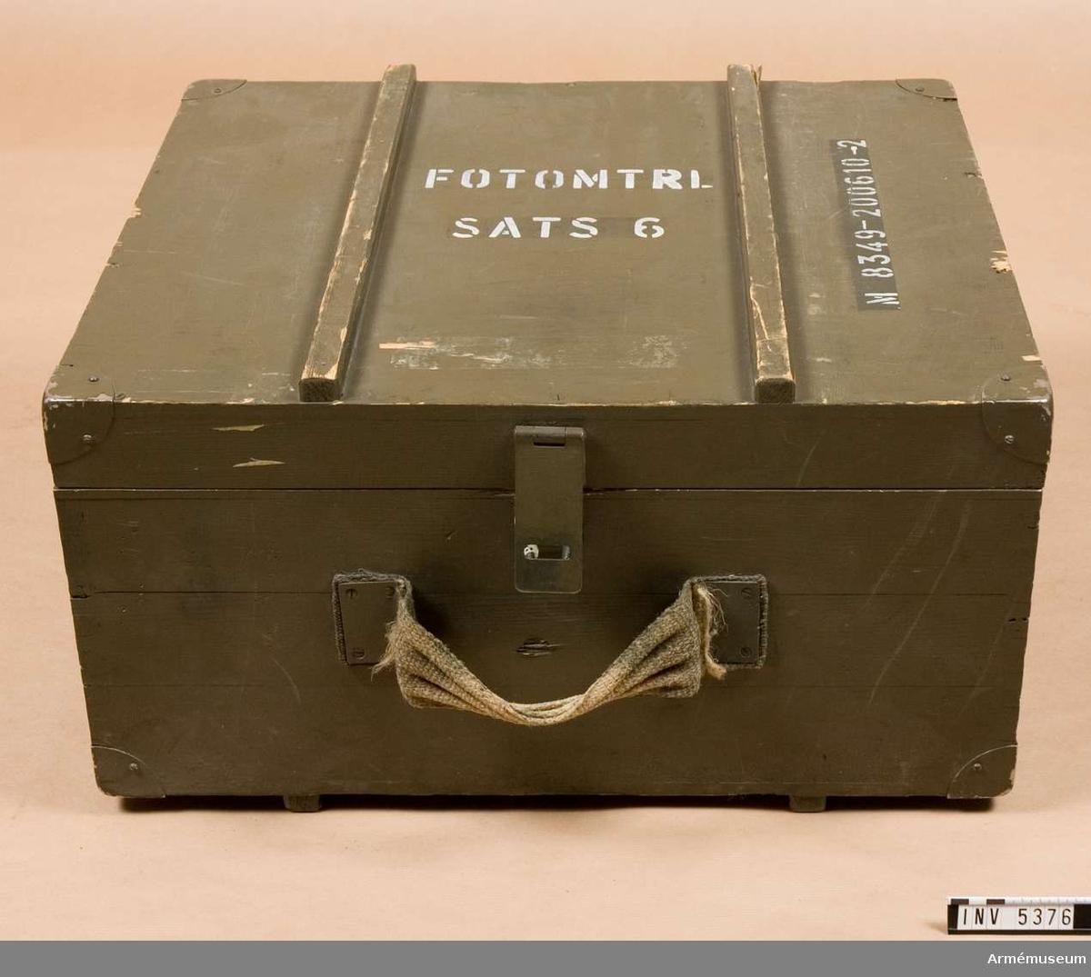 Låda M 8349-200610-2 f fotografisk utrustning.Låda i trä med med bärhandtag i säckväv och anordning för förslutning av metall, låsbar med hänglås. Två gångjärn. Två slitlister på bredsidorna. Färg armégrön med vit text. Insidan är trägul, klarlackad. Märkt SATS 6  FOTOMTRL . Gott skick.Samtliga föremål 1975:5300-75 var förpackade i denna låda.        1992-02-27 packad i låda / Erik Walberg.
