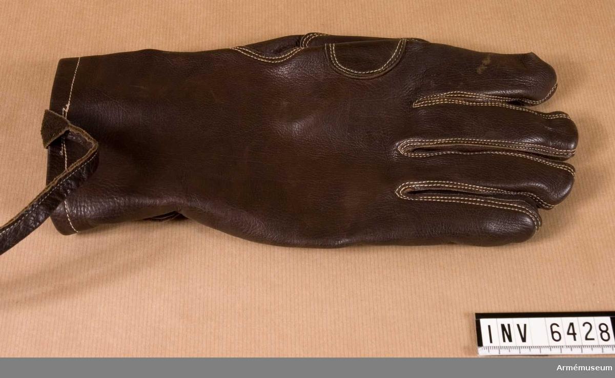 Handske m/1929, ytter- f kavalleri. Stl -. Av mörkbrunt läder m rem f fastsättning vid handleden och rem f åtdragning vid handleden. Extra förstärkning i handflatan. Sömmen är ljus.