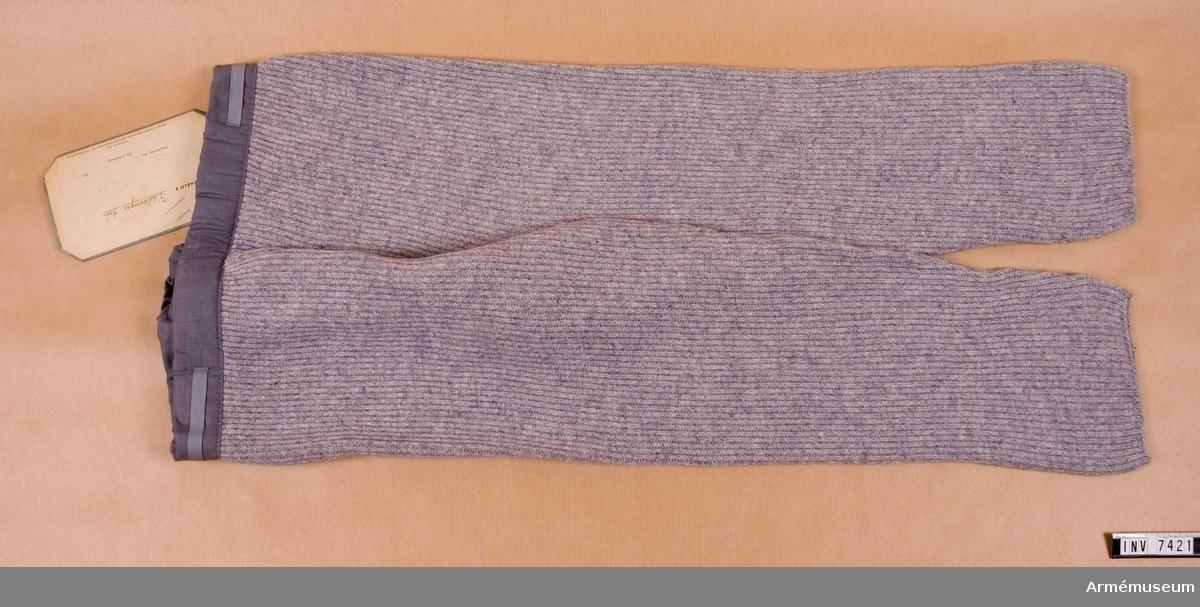 Grova yllekalsonger som slutar under knäet. Upptill en linning genomdragen med strumpebandsresår, alltså reglerbar midjevidd. Hankar av grått bomullsband i sidorna. Storlek 3.