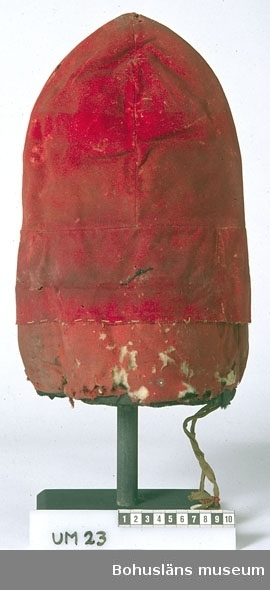 """Toppig mössa av rött, styckfärgat kläde och rött, tunt, kypertvävt ylletyg fodrad med skinn av två olika slag. Mössans övre del består av fyra kilar, av kläde, sammansydda till en toppig form. Delen av kilar är fastsydd vid en ca 8 cm bred remsa av samma tyg. Den har ingen invikt kant, utan är nära traskanten fasttråcklad vid mössans nedre del som är en något smalare remsa av kypertmönstrat handvävt ylletyg, vadderad med ett lager av ull (ca 10 cm brett lager). Fodret är av brunsvart skinn i toppen och mellandelen, troligen barkgarvat renskinn,  och längst ner en ca 10 cm bred remsa av ljust gulbeige skinn med rester av millimeterlånga hår, möjligen ursprungligen ett finare pälsskinn, kanske mårdskinn. Mössan är kantad med svart glansigt ylleband, som är fastsytt runt skinnremsans kant. Den nedre skinnremsan är också kantad med yllebandet längs andra sidan, d v s synligt inuti mössan.  Alla sömmar är handsydda. Ca 10 cm från toppen kan man skönja att ett 28 mm ljusare bandliknande parti runtom. Kan mössan kan ha varit prydd med ett band, en tyg- eller skinnremsa?  På ett ställe är ett brunt, 1 cm brett band, fastsytt vid nederkanten. Ca 15 cm långa bandändar hänger ner. Vid dem är en liten rund papperslapp i metallram, märkt 104, fäst. En svart trådände som troligen varit till en annan gammal etikett finns högre upp på mössan. Mycket sliten. Maläten, ylletyget på nedre delen har stora hål. Även insektsangrepp i toppen och på andra ställen här och var. Smutsig och fläckig. Blekt.  Ur handskrivna katalogen 1957-1958: Lappmössa fr. Lappland Mått c:a 34,5 x 27,5 cm. Rött tyg på läderstomme. """"Toppig"""" modell. Malhål.  Ur Knut Adrian Anderssons katalog 1916: """"No 2. Röd lappmössa tillhört Hambergska samlingarna. Sk. 1870.""""  Lappkatalog: 7 N P, Med. Dr/Riddar"""