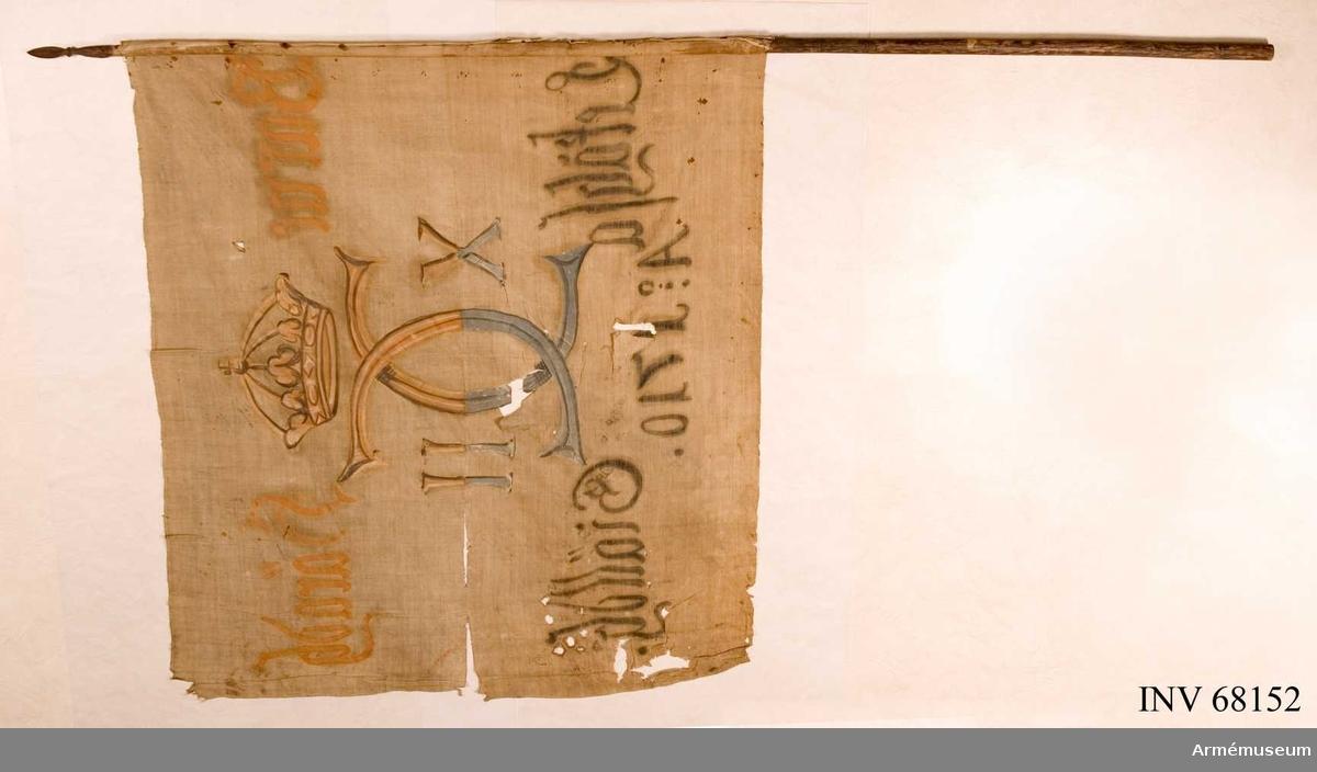 Duk: Tillverkad av enkel vit linnelärft, sydd av två horisontella våder. (Dukens ytterfåll lagd åt dukens insida). Fäst vid stången med en rad järnnagel på ett vitt linneband.  Dekor: Målad endast på dukens insida, i mitten Carl XII:s namnchiffer, dubbelt C med X - II på ömse sidor, krönt med sluten krona. På den övre våden i gult och brunt, på den nedre i blått och svart. Text på ömse sidor om chiffret, upptill i gult och nedtill i svart. Under chiffret text i svart.  Stång: Tillverkad av furu. Holk och spets i järn. Spetsen består av ett litet lansettformat blad.
