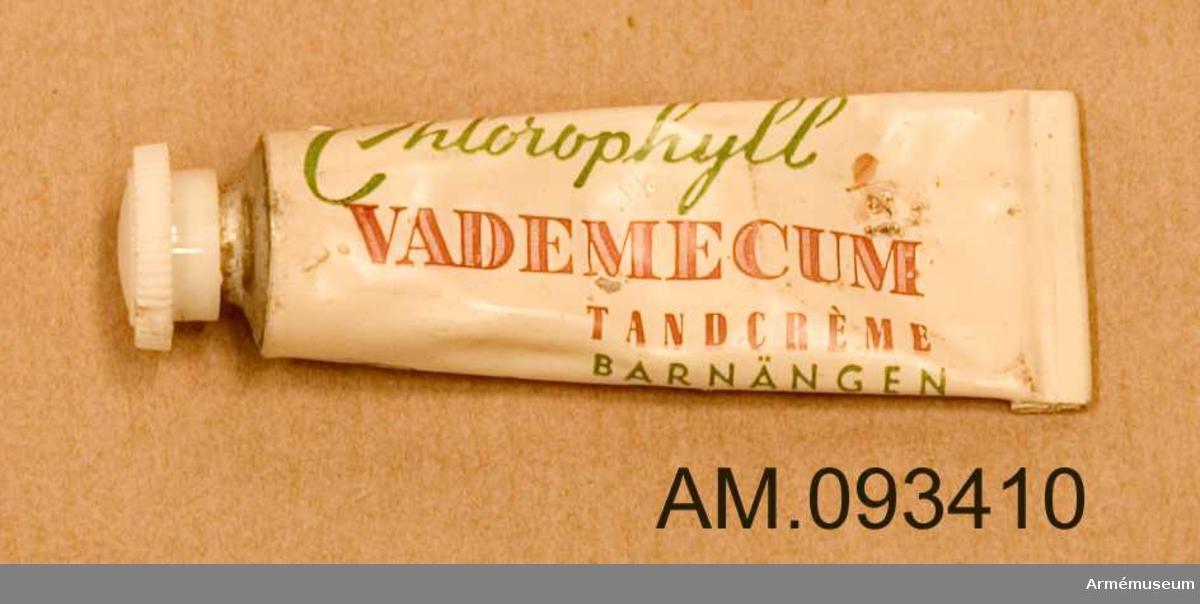 Liten vit tandkrämstub av märket Vademecum med skruvkork och grön och röd text. Innehåller tandkräm.