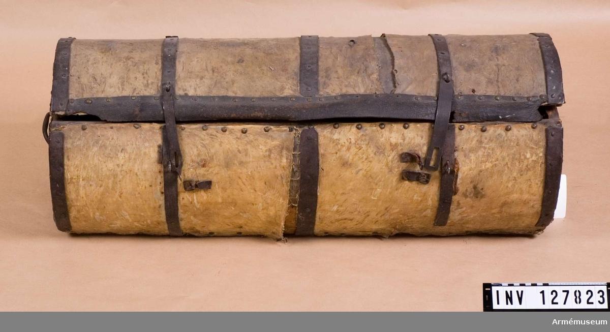 Kista av trä, klädd med gult skinn. Järnbeslag. Likt utförande AM 68/67.