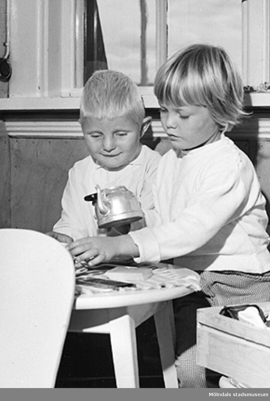 """En pojke och en flicka sitter vid ett """"kaffebord"""". Holtermanska daghemmet 1953."""