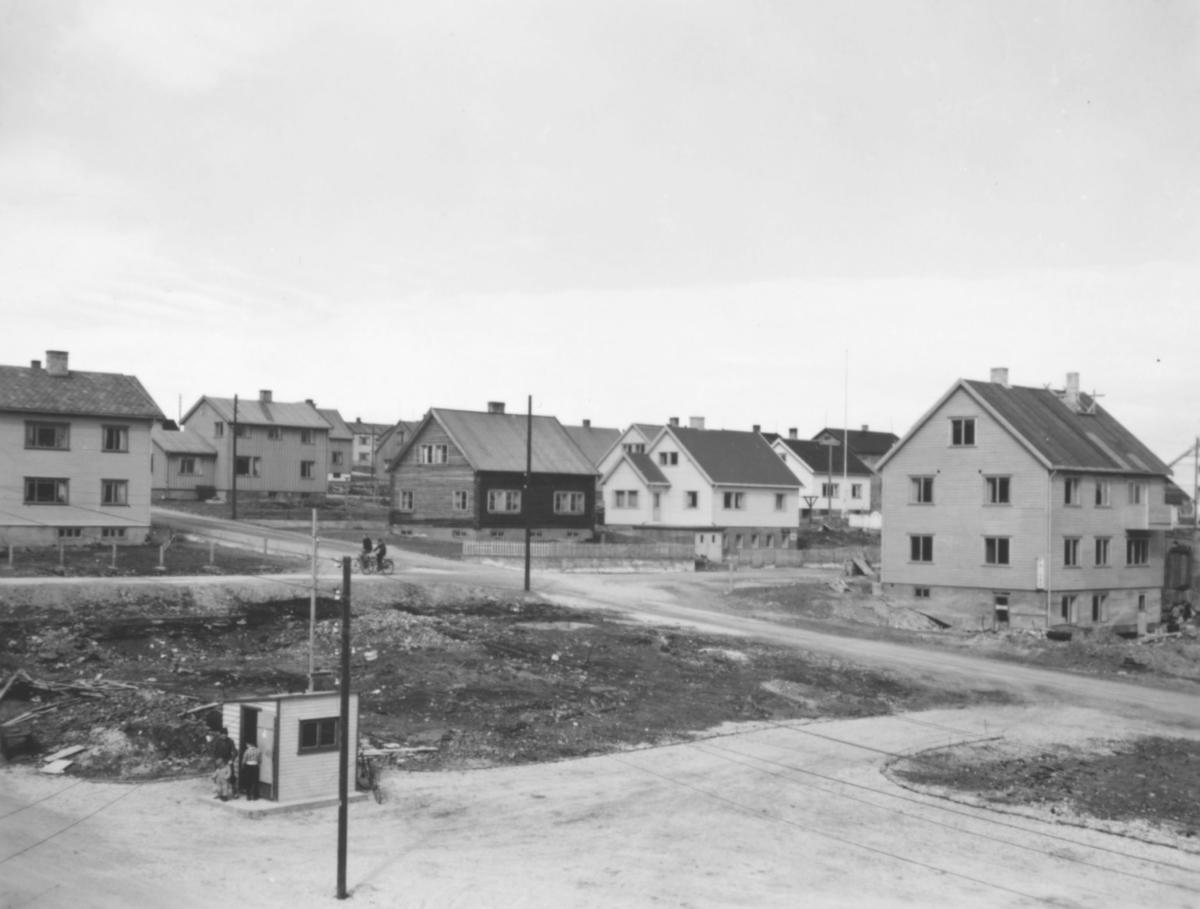 Motiv i fra gjenreisningen av midtbyen i Vadsø etter andre verdenskrig. På bildet ser man flere boliger. En tomt er tom. I den lille bua hvor det står noen personer utenfor var det drosjestasjon. Det er to syklister på grusveien ovenfor tomta