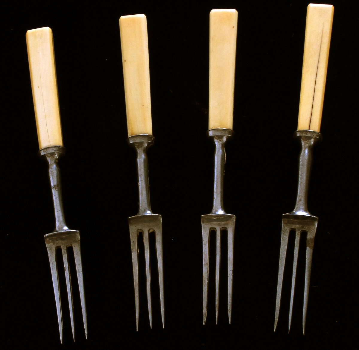 Gafler,  4 stk. Stål  med   ben  skaft.  Tretinnet, fortsetter i smalt stålskaft,  rundt. Benskaft med rette sider. Ustemplet.