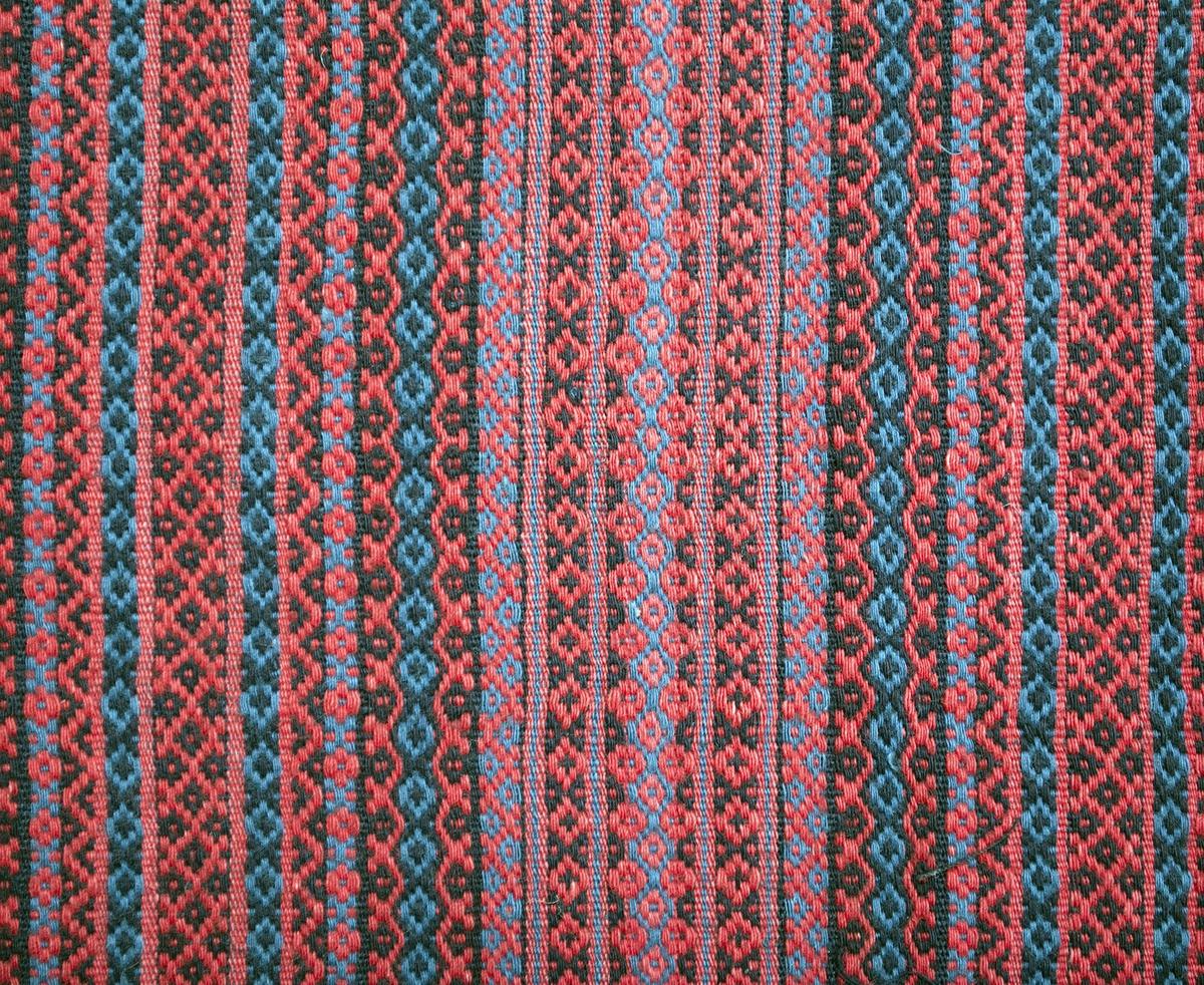 """Randigt förkläde i rosengång och inslagsrips. Mönsterränder i rött, blått och svart. Smala ripsränder mellan rosengångsränderna. Smal fåll i sidorna som är avslutade med en inslagsrand i grönt. Invikt stadkant nedtill och 17 mm bred fåll. Förklädet är rynkat upptill mot linningen. Tyget i linningen är vävt i inslagsrips med ränder i blått, rött svart och vitt. På framsidan av linningen är ett opphämtavävt band påsytt. Knytbandet är mönstrat med stjärnor, snedrutor med taggar och korsformer i blårött på blå botten. I sin helhet är bandet 2990 mm långt. I var ände är bandet avslutat med tre tofsar som sitter på varsin ögla av lindade varptrådar. Förklädets bredd vid linningen: 360 mm. Bandet är 1730 mm långt i en sida och 900 mm långt i den andra sidan. Varp i blått lin- eller bomullsgarn, 11 trådar/cm. Inslag i rött, blått och svart 1-trådigt bomullsgarn, ca 60 inslag/cm. Bandet: Varp i blått bomullsgarn samt i blårött/rosa ullgarn. Inslag i blått bomullsgarn. Bandet troligtvis senare  än förklädet. Märkt på baksidan, nedtill i ena hörnet, med en påsydd tyglapp med texten: """"Torna h-d  N° 233 a""""."""