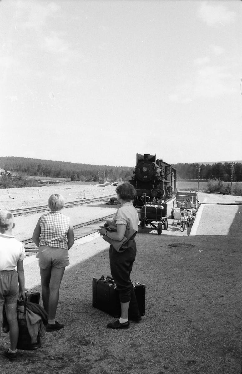 Rørosbanens sørgående dagtog, tog 302, Trondheim - Oslo o/Røros, på vei inn på Os stasjon. Damplokomotiv 26c 413. Nye Os stasjon var fortsatt under utbygging, lasterampe-sporet var ikke ferdig.