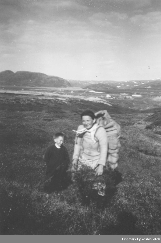 Serine Nikodemusen bærer en sekk torv til brendsel på vei ned fra torvemyra i Kokelvdalen. Som følge har hun sønnen Nils Nikodemusen. I bakgrunnen ses flere hus og bygninger