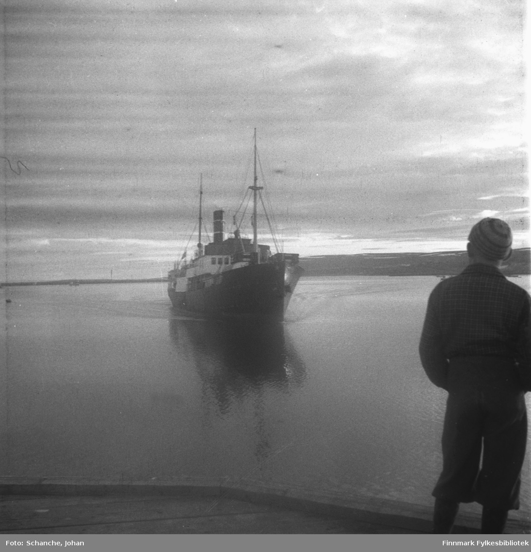 Ung gutt står på kaia i Vadsø og ser på  hurtigrute 'Polarlys' som er på veg mot kaia. Vannet står stille.