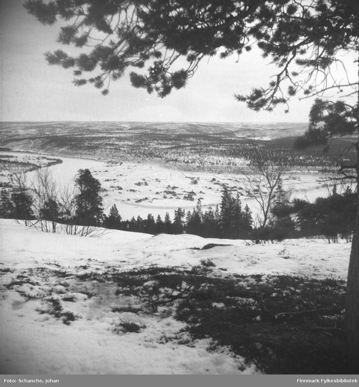 Oversiktsbilder over Karasjok tatt fra fjellet ned mot bygda i dalen.  Fotografen har stått under en stor furu, furugrein henger over landskapet på bildet.  Samme motiv som i FBib.95066-105. På dette bildet ser vi også en del av trestammen.
