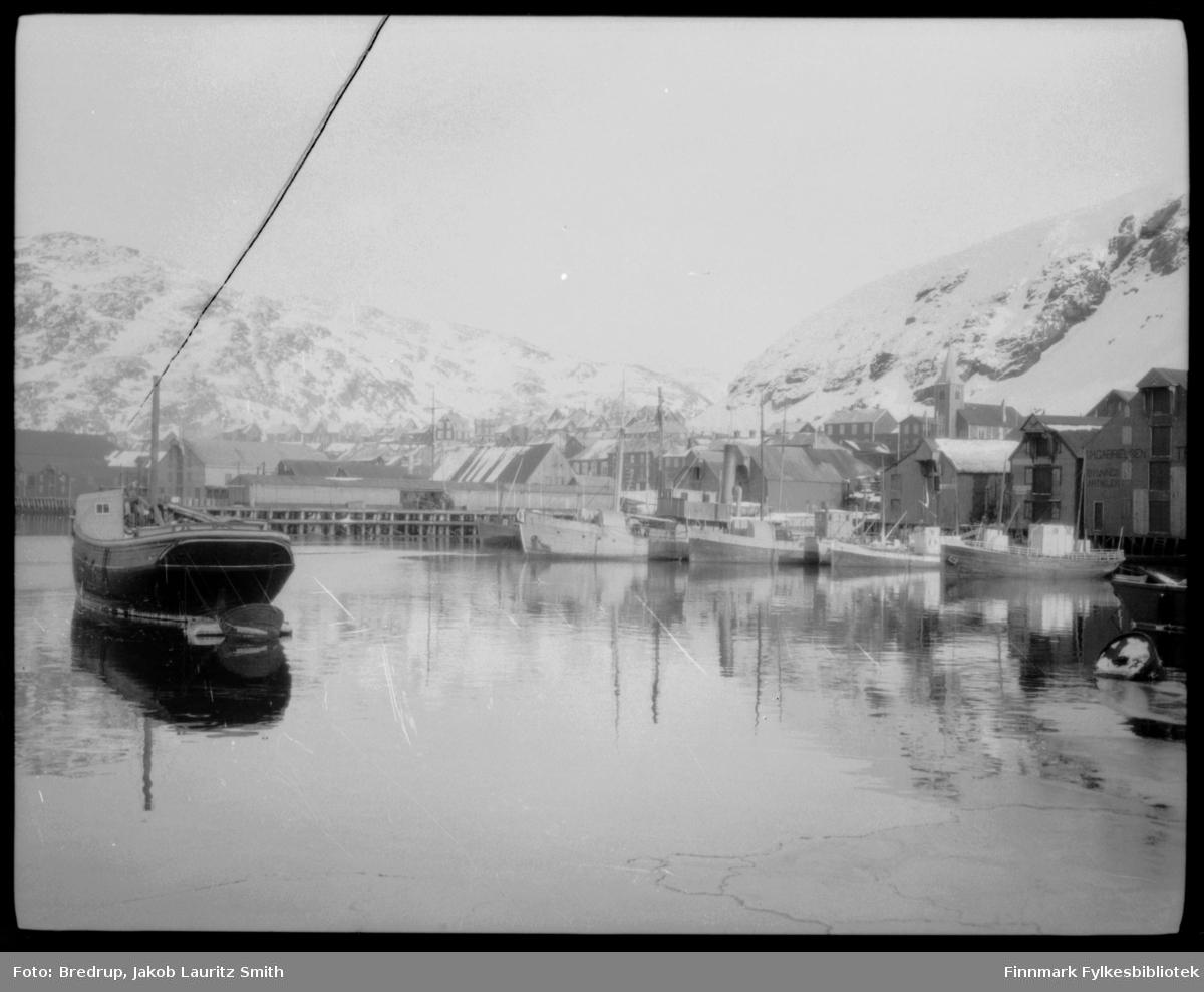 Oversiktsbilde av havna i Hammerfest.  I bakgrunnen bybebyggelse, bl.a. kirka.  I Øyfolk 1996 har bildet denne teksten: Parti fra indre havn mot dampskipskaia.  Fartøyet til venstre het 'Emil' tilhørende Feddersen & Nissen.  Dette var et gammelt pomorfartøy som Burckow flyktet med fra Russland under revolusjonen i 1917.  Fartøyet ble nedrigget og bl.a. slept rundt om til småsteder i Vest-Finnmark for oppkjøp av tørrfisk og saltfisk