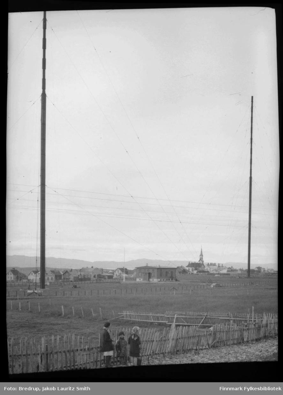 Tre jenter står ved inngjerdet innmark. Bak dem står kringkastingshus og radiomastene.  Bakerst en del av byen, kirke til høyre.