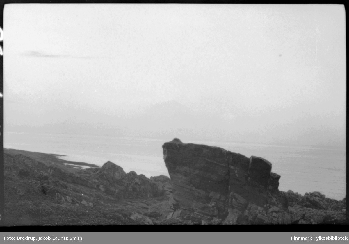 Bildet er fotografert fra en høyde ned mot havet.  Landskapet er fullt av steiner og klipper, midt i bildet dominerer en stor stein.  Bildet kan være tatt mange steder i Finnmark.