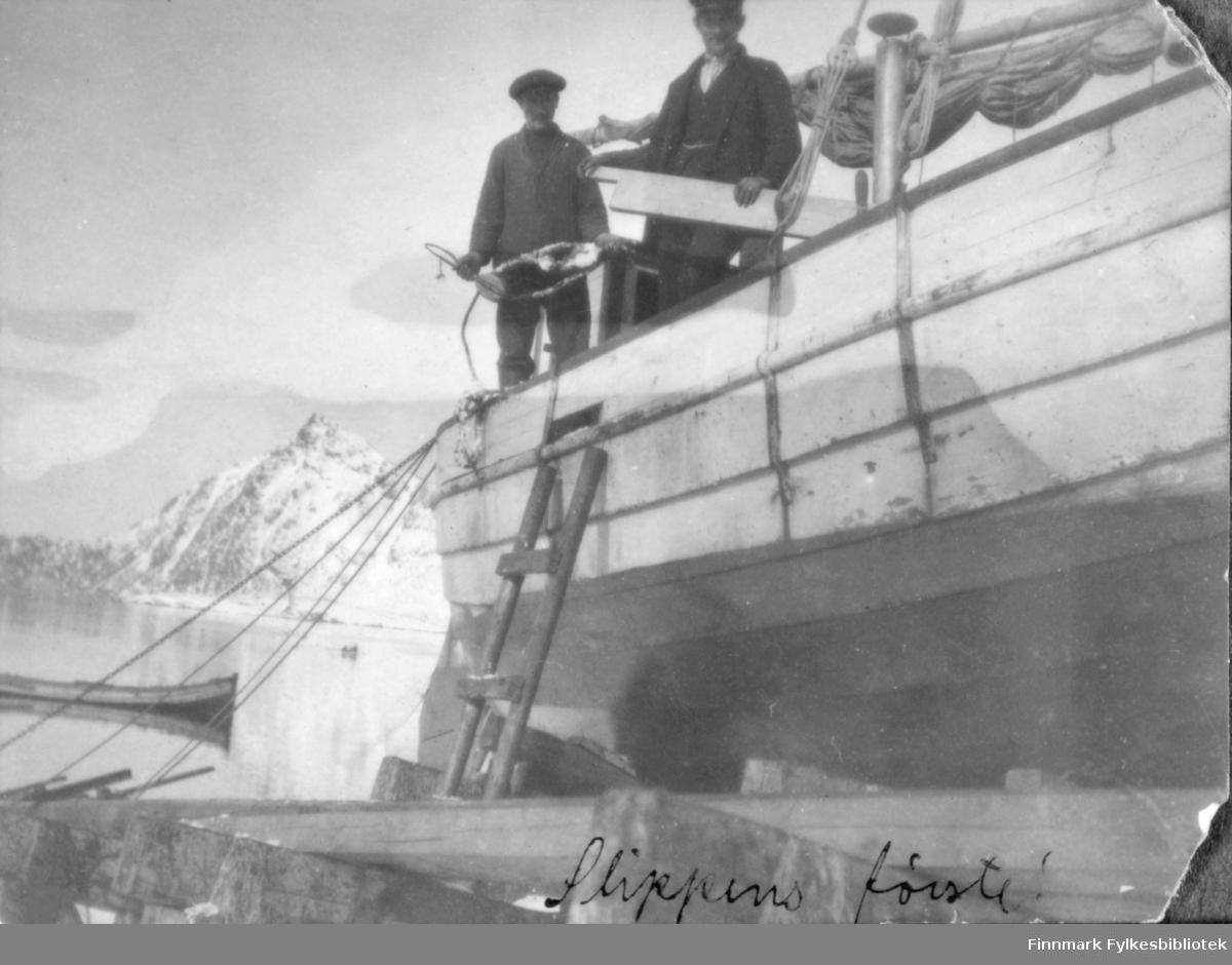 'Slippens første!' - båt trukket opp på land mens to menn arbeider med den. Bergsfjord, ca 1915-1920