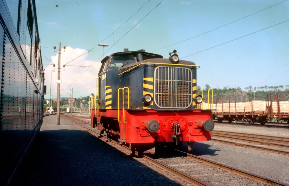 """Norsk Hydro skiftelokomotiv inne på skifteområdet på Herøya. """"Farvel til type 66"""". Ekstratog for Norsk Jernbaneklubb med ekspresstogsett type 66, motorvogn BM 66 01, mellomvogn B66 og styrevogn BS66 63. Turen gikk Oslo V - Horten - Brevik - Skien - Kongsberg - Oslo V, og ble kjørt noen dager etter at togsettene var tatt ut av trafikk."""