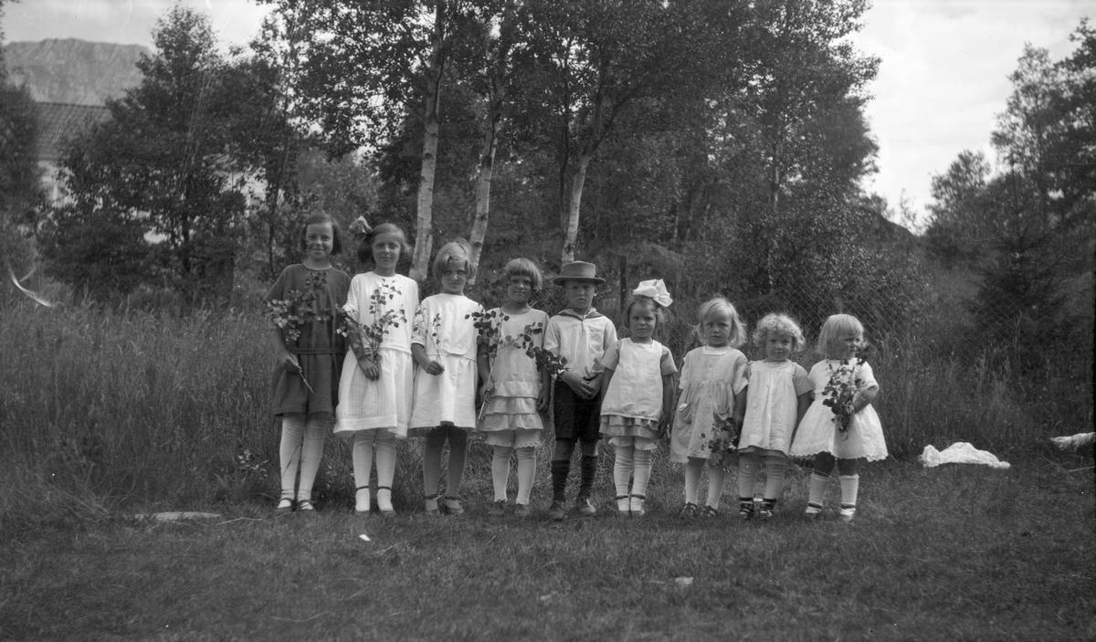 9 småbarn. 8 jenter og en gutt. Jentene står på en rekke, og gutten står i midten med en hatt på hodet.  Trær,et hus og fjell i bakgrunnen.