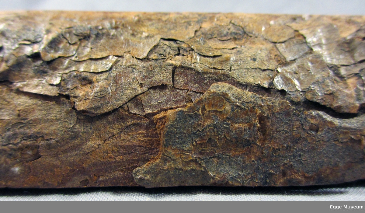 Vedprøve fra Lerk som viser radialsnitt, et tangentialsnitt og tverrsnitt. Prøven er med bark. Alle treflater er pusset og lakkert. Artsnavn er stemplet? på (så lakkert over). Brukt i undervisninga ved Skogskolen på Steinkjer.