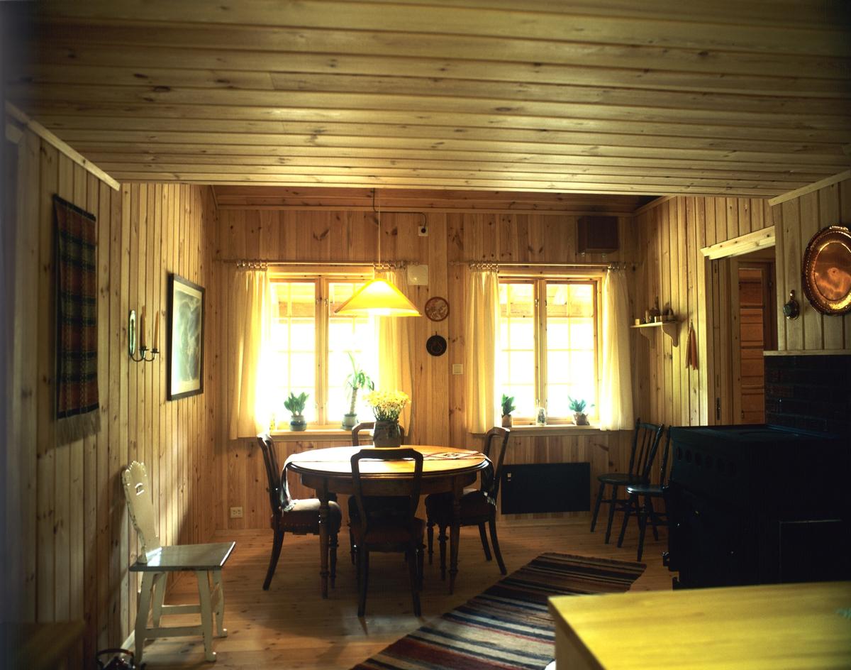 Del av stue med bord og stoler. Furupanel i tak og vegger. Illustrasjonsbilde fra Nye Bonytt 1984.