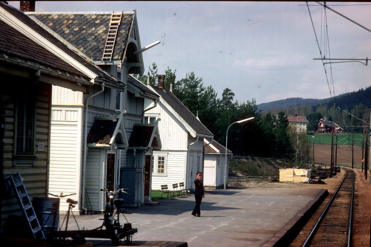 Tog 601 passerer Sokna stasjon. Togekspeditør på plattformen.