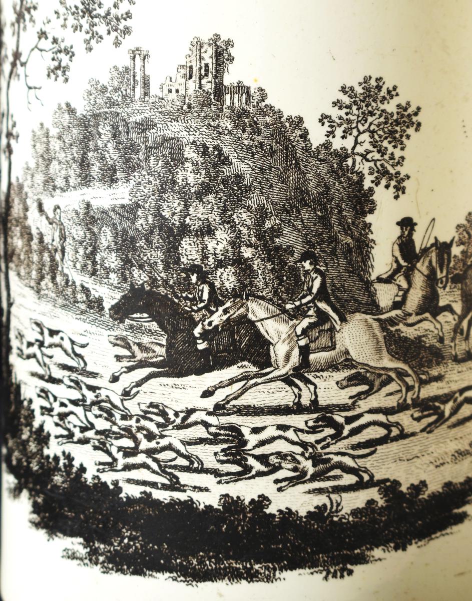 hovedmotivet: revejakt  i engelsk parklandskap m/ ruin  på en høyde, flankert av et par spinkle  buketter av haveblomster.