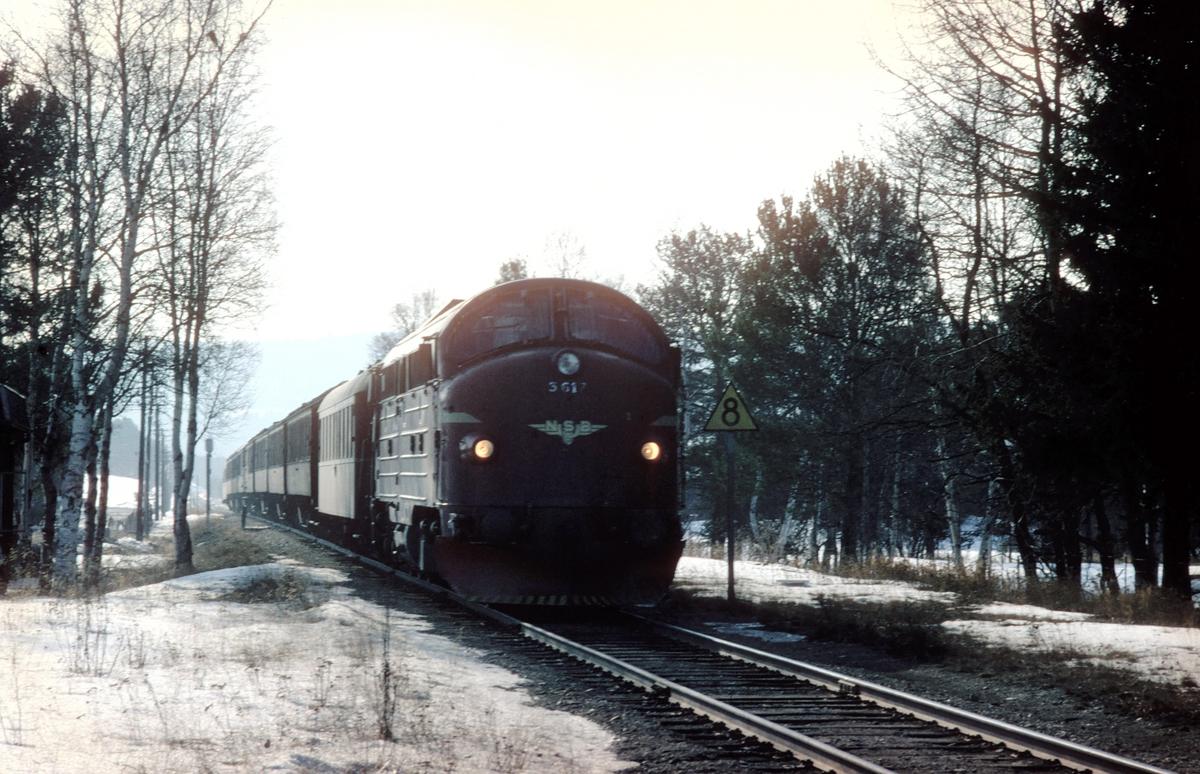 """Ekstra persontog (påsketog) Oslo Ø - Røros ankommer Os stasjon, Os i Østerdalen, palmelørdag 1979, der det skal krysse tog 302. NSB dieselelektrisk lokomotiv Di 3a 617 med trevogner og to stålvogner litra B1. Vognene i toget gikk på hverdager i et togpar mellom Moss og Oslo Ø, det såkalte """"Ormen Lange"""", men ble brukt som innsatsmateriell ved høytider på lengre strekninger."""