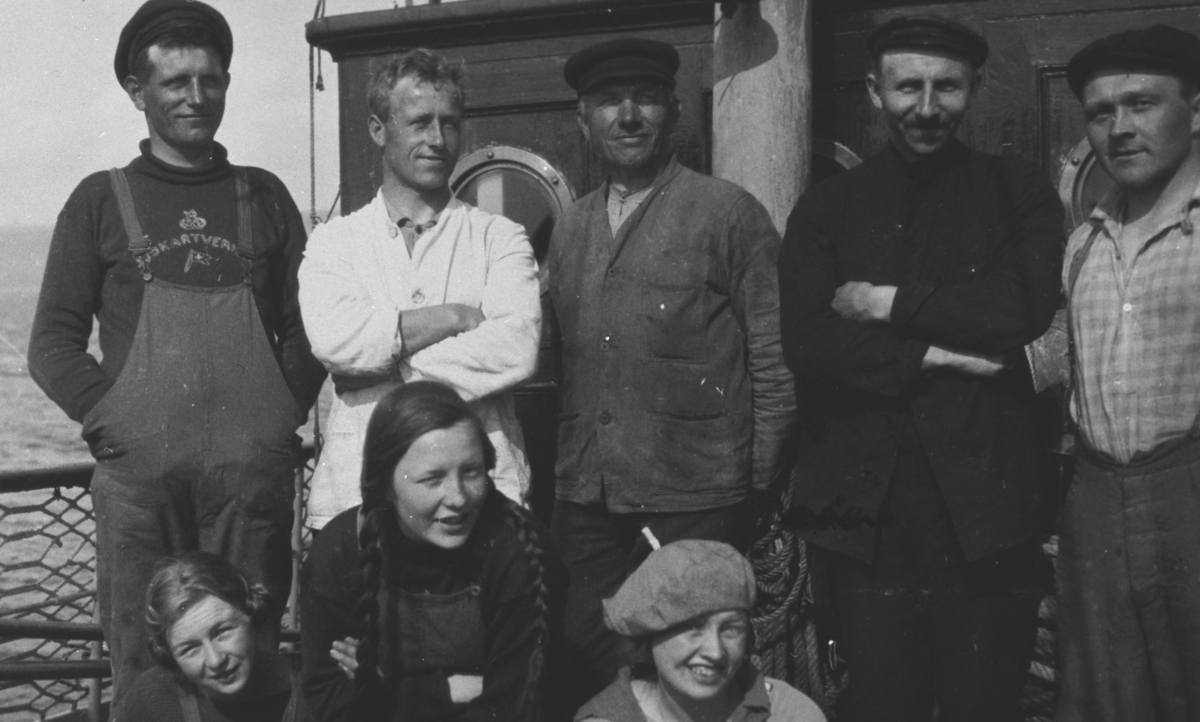 """Et gruppebilde fotografert på oppmålinsfartøy """"Wilhelm Huth"""". Bakerst står mannskapet Hans, Ola, Myklebust, Eriksen og Jøran. Føran jentene Eva, Biddi Hermansen og Ingrid Hermansen."""