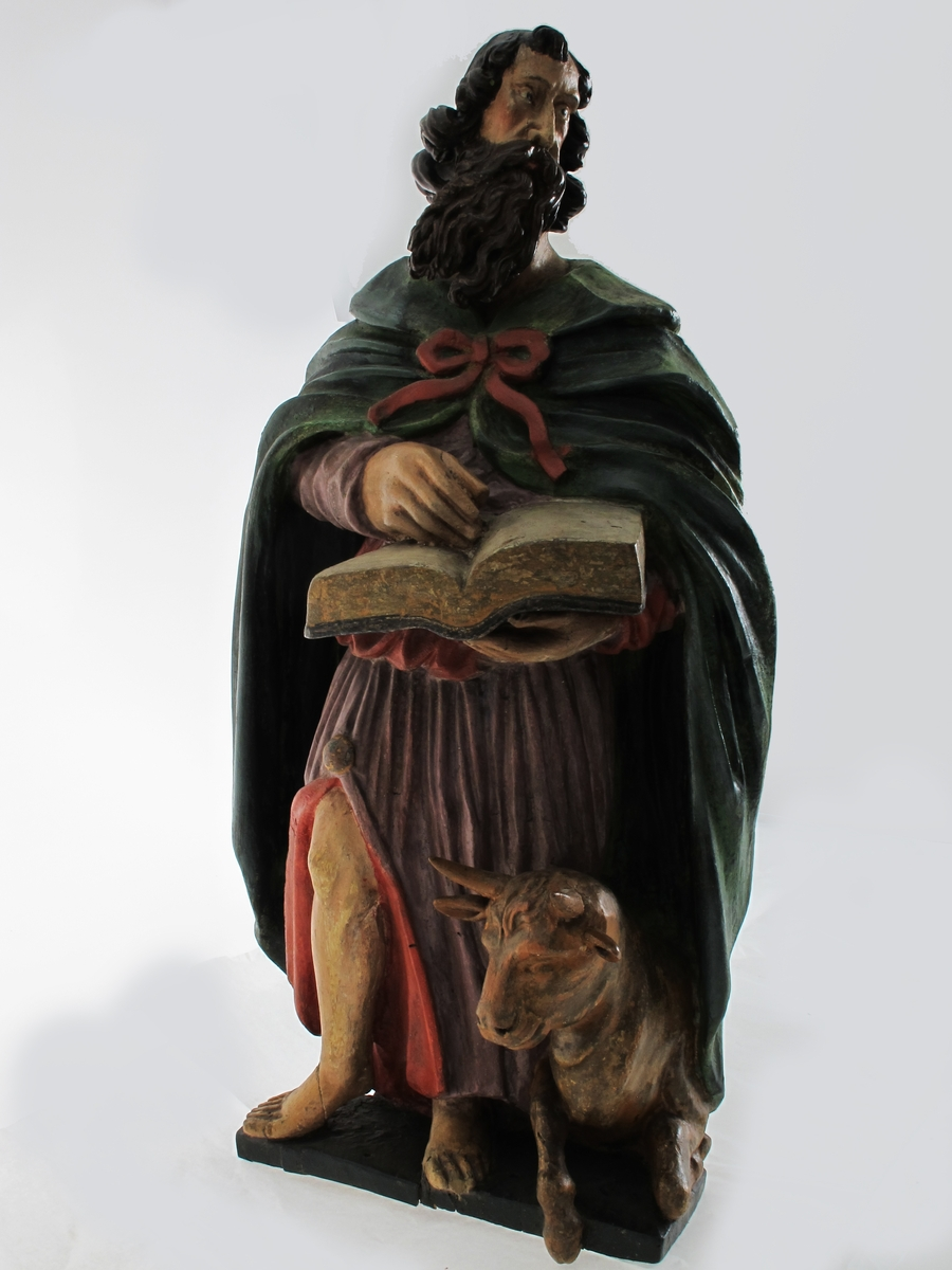 Lukas med oksen. Stående mannsfigur, liggende okse