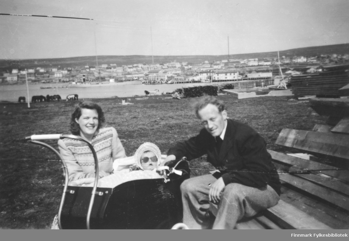 Familien Ebeltoft på landtur på Vadsøya, 1950. Fra venstre Ragnhild, Torill i vogna, og Fritz. I bakgrunnen ser vi den delvis gjenreiste byen. På øysiden ser vi store plankestabler, man skal sikkert til å bygge nye hus her også. Hester beiter nærmere fjæra