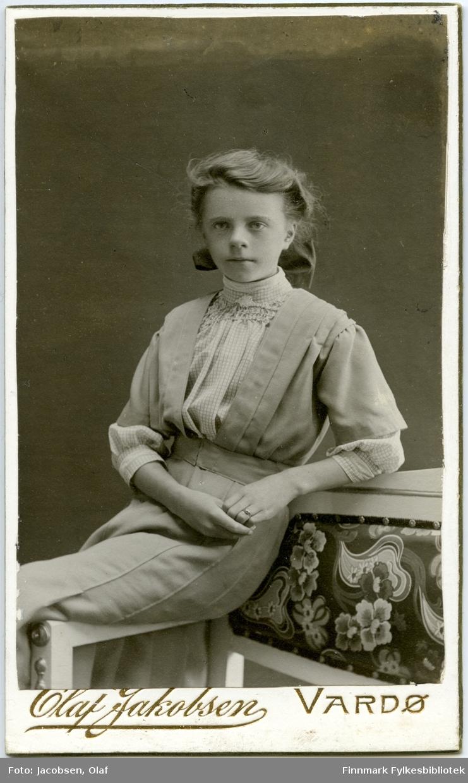 Visitkort. Portrett fra en ung kvinne. Personen ukjent. Hun sitter på armlenen av en sofa og er kledd i en lys kjole.