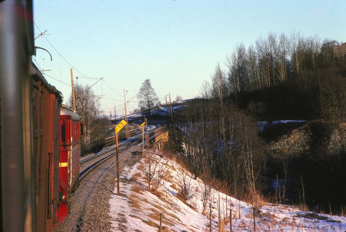 Tog 301, dagtoget Oslo - Trondheim over Røros, kjører inn på Børke bru mellom Leirsund og Frogner. Innkjørhovedsignalet på Frogner stasjon kan sees på bilde. Lokomotiv type El 11.