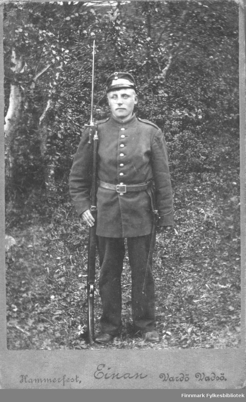 Portrett av ukjent soldat i menig infanteriunifrom med gevær med bajonett, fotografert utendørs av fotograf Einan, Hammerfest/Vardø/Vadsø.