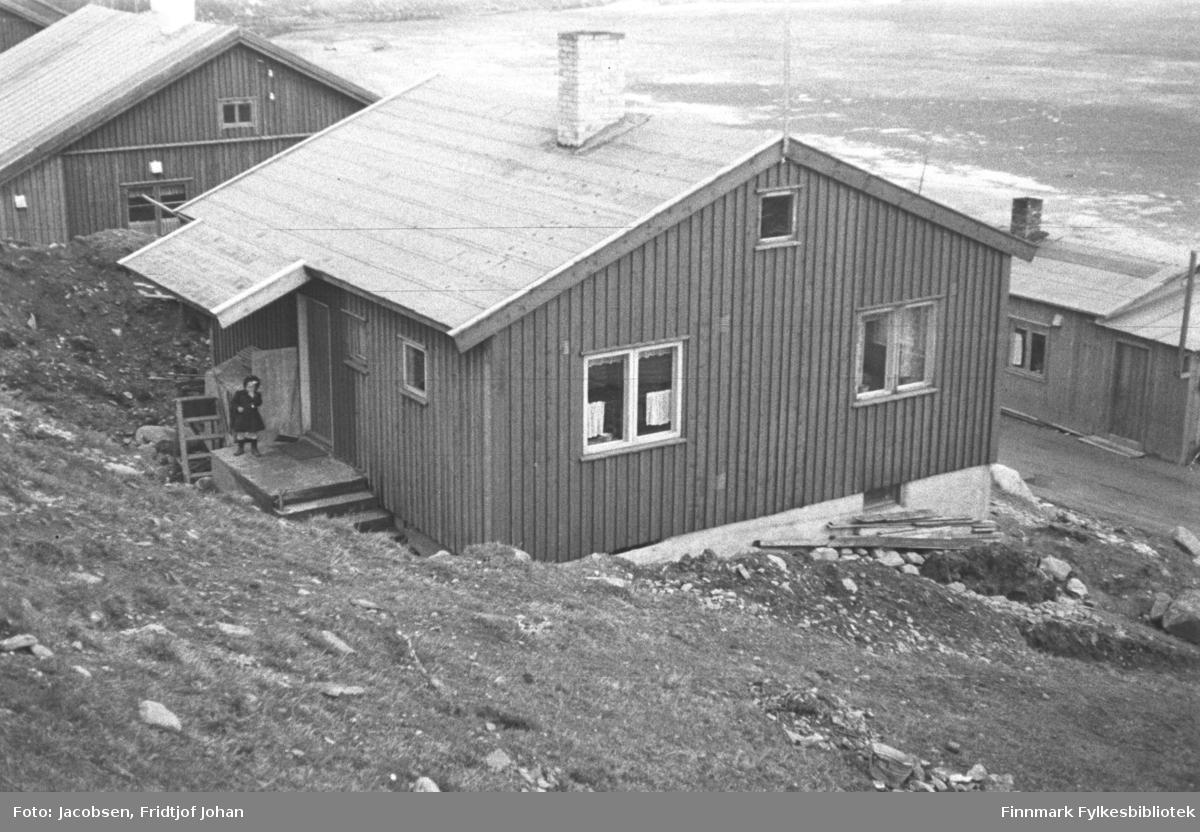Storvannsveien 2. Huset ble bygget av Alf Edvard Jacobsen, Fridtjofs bror. Jenta på trammen er Ragnhild Jacobsen, nå gift Antonsen. Hun har en mørk kjole og mørk lue på seg. Familien flyttet inn i 1948. Den 1.desember 1950 ble huset overtatt av Fridtjof Jacobsen senior, faren til Alf Edvard, Ragnvald og Fridtjof Johan. Huset oppe til venstre på bildet tilhørte det som den gang het Telegrafverket. På nedsiden av Storvannsveien står brakka til Peder Dahl og det delvis islagte Storvannet ses i bakgrunnen. Terrenget bak husene er ganske bratt og delvis gressdekt.