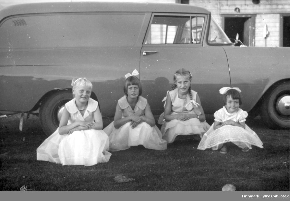 Fire kusiner poserer med sine nye finkjoler. Fra Venstre til høyre: søstrene Reidun Stock og Ruth Stock. Ved siden av sitter Elin Rushfeldt og Svanhild Rushfeldt. Kjolestoffet er blitt sendt fra familie i Amerika. Kjolene var ferdigsydde (unntatt Svanhilds, som var kjøpt) og bildet skulle senere sendes tilbake til familien i Amerika. Jentene sitter foran en bil (Opel Olympia varebil årsmodell1958-60) og i bakgrunnen kan man se et hus. Kusineflokken har pyntet seg til annledningen med smykker og hårsløyfer.