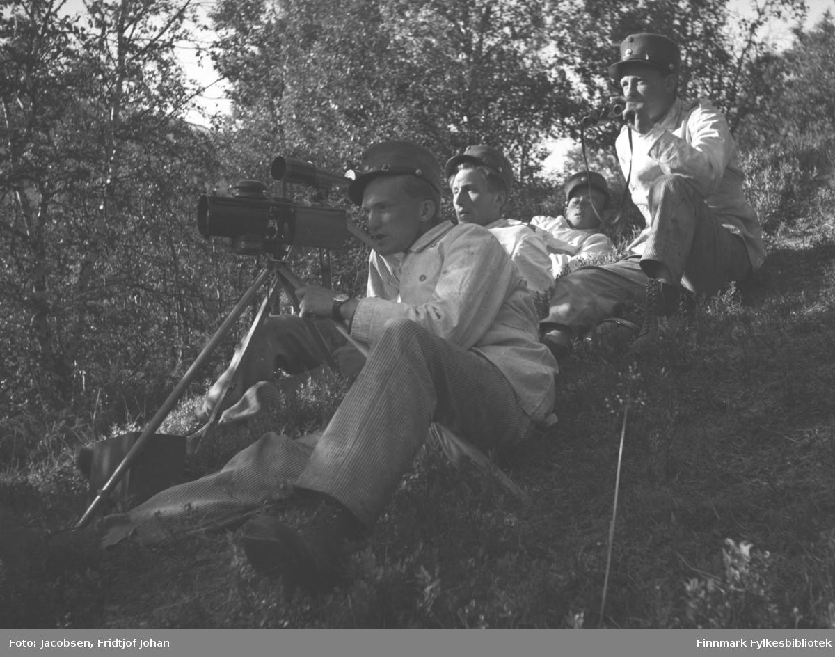 Fridtjof Jacobsen sitter fremst med siktekikkert som står på et stativ. Tre andre menn sitter på bakken bak han, alle med like uniformer på. Mannen rett bak har en kikkert i sin venstre hånd. Terrenget der de sitter skrår litt og er gress- og lyngdekt. Det er ganske tett med løvtrær rundt dem. Bildet er sannsynligvis fra militærtjenesten hans eller en øvelse han deltok på og er nok fotografert i Alta like før andre verdenskrig.