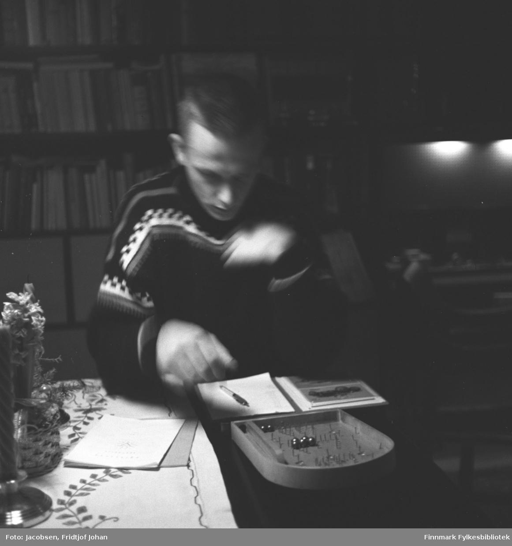 Arne Jacobsen spiller et spill. Spillet ligger på det mørke stuebordet sammen med en blokk, en pen, en blomsterdekorasjon og lysestaker. Han har en mørk genser med lyst mønster oppe. Bak han står en stor veggseksjon med mange bøker og noen pynteting i hyllene.
