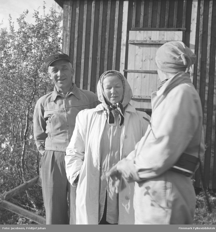 Tre personer står foran en hyttevegg. Til venstre står Alf Pedersen. Han har en lys jakke, litt mørkere bukse og mørk skyggelue på seg. Ved siden av står Berthe Wara iført en lys kåpe og tørkle på hodet. Til høyre står Aase Jacobsen, også hun i en lys kåpe og tørkle på hodet. Mye gress og lyng på bakken og løvtrær står til venstre på bildet. Fotografiet kan være tatt i Bjørnlia i Repparfjord