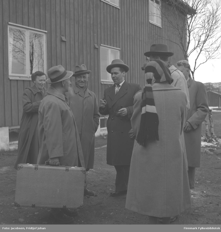 En gruppe mennesker (telegrafverksansatte) står utenfor et hus som kan være Lakselv Gjestgiveri. Nummer tre fra venstre er Alf Henriksen, kontorsjef i Telegrafverket (som det het til 1969), og ved siden av ham står Bjarne Pedersen. Kvinnen med skjerf på hodet og ryggen til er sannsynligvis Aase Randi Jacobsen. Bildet er sannsynligvis tatt i forbindelse med en tur flere telegrafverksansatte var på rundt 1960 og de bodde da på gjestgiveriet i Lakselv.