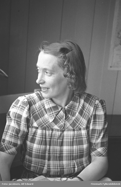 Aase Jacobsen fotografert i Lødingen sommeren 1945. Hun har en rutet og kortermet bluse på seg. Hun har en hårnål på venstre side av hodet. Noe lyst tøy med mønster ses nederst på bildet, kan være en duk eller noe håndarbeide. Panelet på veggen bak henne kan se ut som koreapanel. En plakat eller kalender kan ses på veggen helt til høyre på bildet.