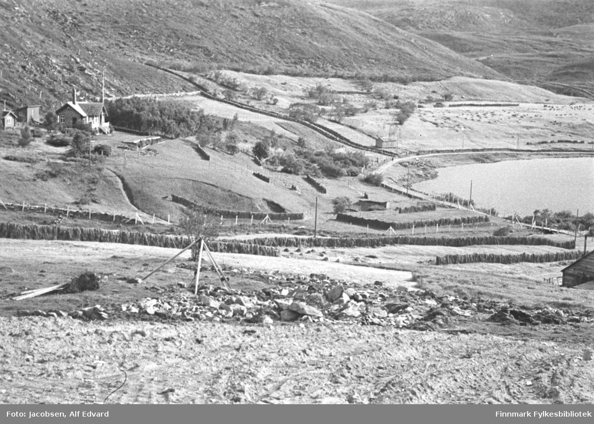 Bilde fra Storvannsområdet. Oppe til venstre på bildet, på Nissen-jordet, står Nissen-hytta. Hytta har en høy skorstein og en flaggstang i røstet på tilbygget. Bak den står to mindre bygg. Nærmest kamera er Kalland-stykket. Den lille bekken som renner til venstre for Nissen-hytta er grensen mellom eiendommene. Røstveggen på et lite bygg ses nede til høyre på bildet og det er mange hesjer med høy hengt opp. Stokkene som er satt opp som en trekant er en stubbebryter. Området lengst fra kamera, oppe til høyre, er Einan-stykket, omtrent der Bybo-blokka står i dag. En liten vik av Storvannet ses til høyre på bildet.
