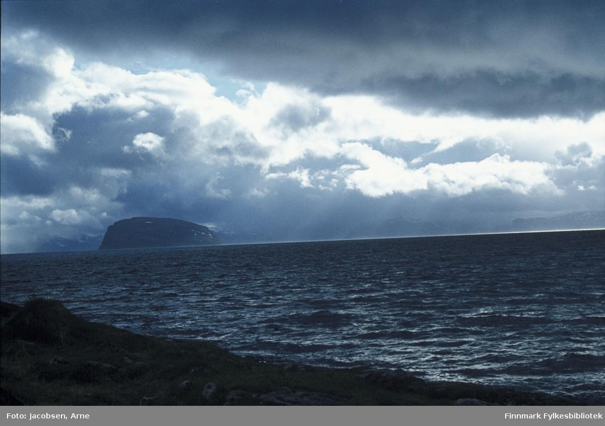 Den karakteristiske formen på øya Håja vises mot tunge skyer, sett fra Kvaløya. Sørøya skimtes såvidt i bakgrunnen. Noe vind, men oppholdsvær. Bildet er nok tatt en sen vårdag/tidlig sommer pga. snøflekkene som ligger igjen på øya.