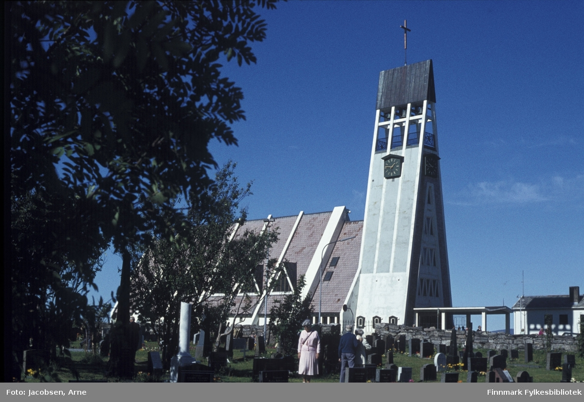 Hammerfest kirke i sol og klarvær. Foran ses kirkegården med besøkende. Nederst til høyre vises presteboligen. Kirken ble bygget i 1961 på omtrent samme plass som kirken som ble brent av tyskerne.
