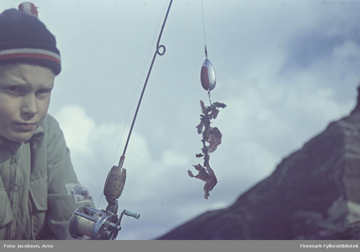 Arne Jacobsen på fisketur. Han har en topplue med dusk og en ganske tykk jakke så temperaturen er nok ikke så høy. Overskyet. Redskapet hans er en vanlig fiskestang med åpen havfiskesnelle og sluk.'Fangsten' er en tare-bit. Et diffust fjellparti vises nederst.
