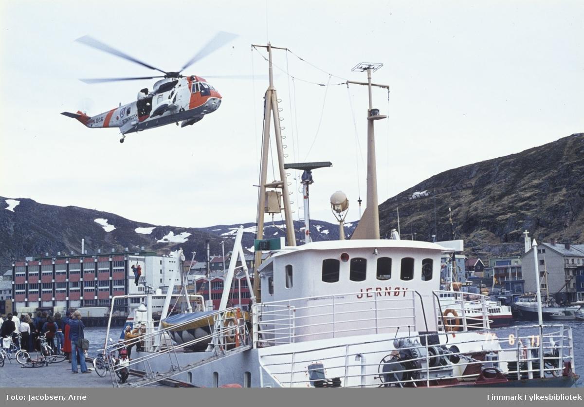 Et Sea-King redningshelikopter demonstrerer redning i Hammerfest indre havn. To personer henger i wiren under helikopteret. En liten gruppe mennesker står på kaia og ser på og noen tråsykler og en moped bak dem. FFR-båten Jernøy ligger ved kai med landgangen ute. Bak hekken til Jernøy ses deler av Findus-anlegget og Mollafjellet i bakgrunnen. Foran rorhuset til Jernøy ligger FFR-båten Brynilen ved Bangkaia. Til høyre for den ligger en stor fiskebåt med en liten plastbåt inntil. I bakgrunnen er fjellet Salen. Noen snøflekker ligger enda på Mollafjellet en tidlig sommerdag.