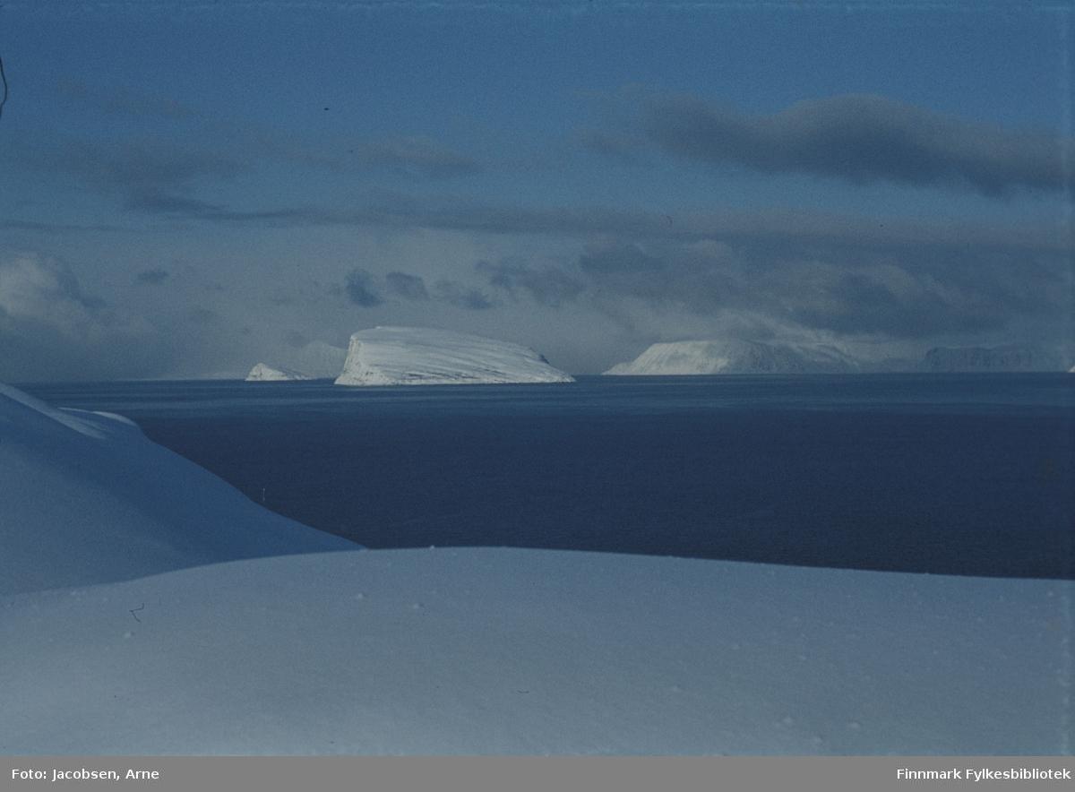 Midt i bildet ses øyene Håja med Hjelmen bak til venstre og Sørøya til høyre. Havområdet som vises er Sørøysundet. Det er mye snø. Oppholdsvær og lite vind. Bildet er tatt fra Bjørkåsen i Rypefjord utenfor Hammerfest